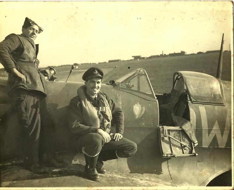 Warren M. Lightbourn kneeling by his airplane